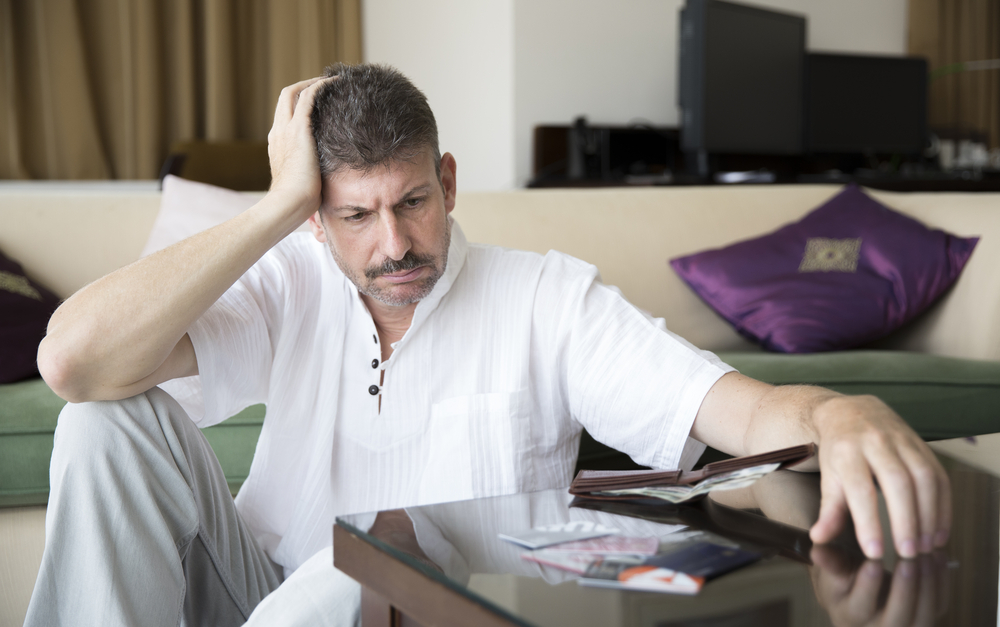 Man worried over bills and cards.