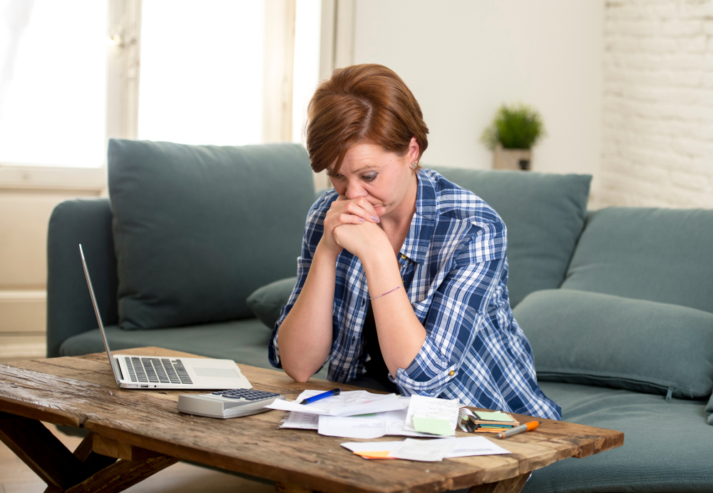 Woman worrying over bills, calculator and laptop,