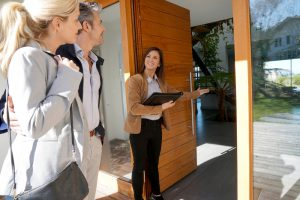Rel estate agent showing a house to a couple.