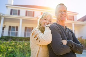 Couple standing in front of home.