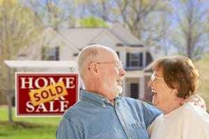 Happy couple in front of house and sign.