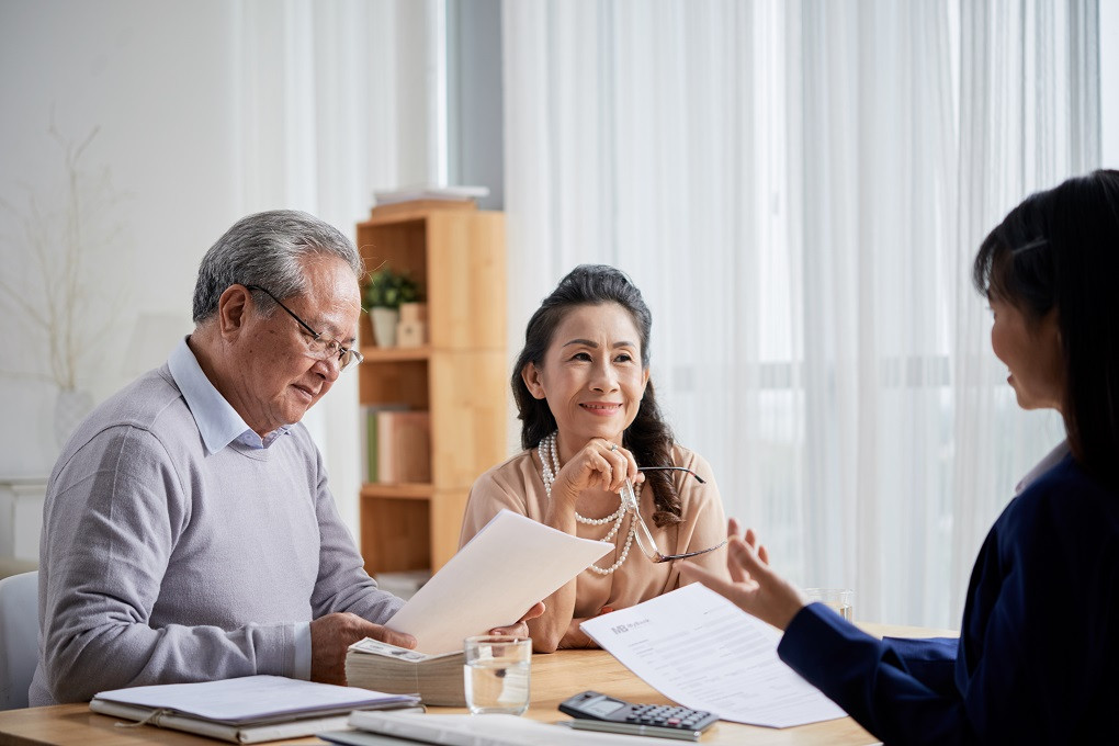 Asian aged couple meeting with real estate agent