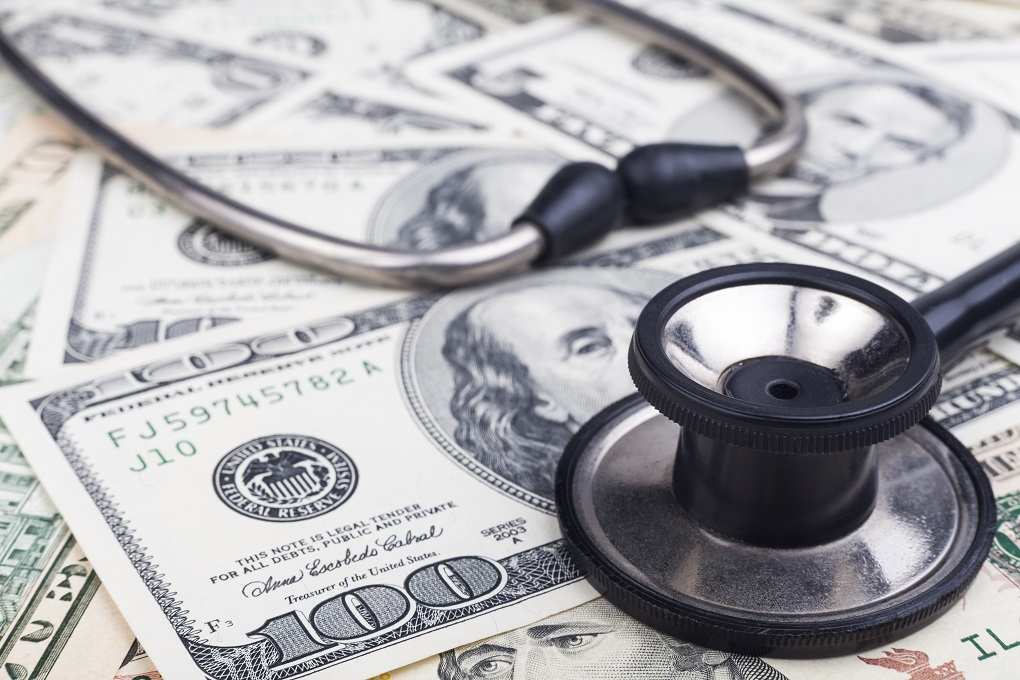 Black stethoscope close-up on top of Dollar banknotes side view