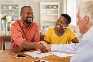 Mature black husband shaking hands with senior agent on taking loan. Happy african couple sealing with handshake a contract with financial advisor for investment. Man making sale purchase deal concluding with a handshake with estate agent.