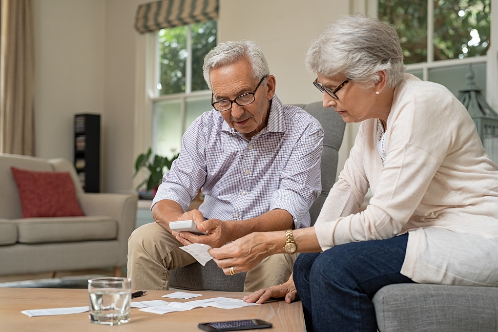 Smiling senior couple with papers, calculators and bills at home. Senior couple calculating taxes at home. Mature man and woman wearing spectacles and looking their expenses together.
