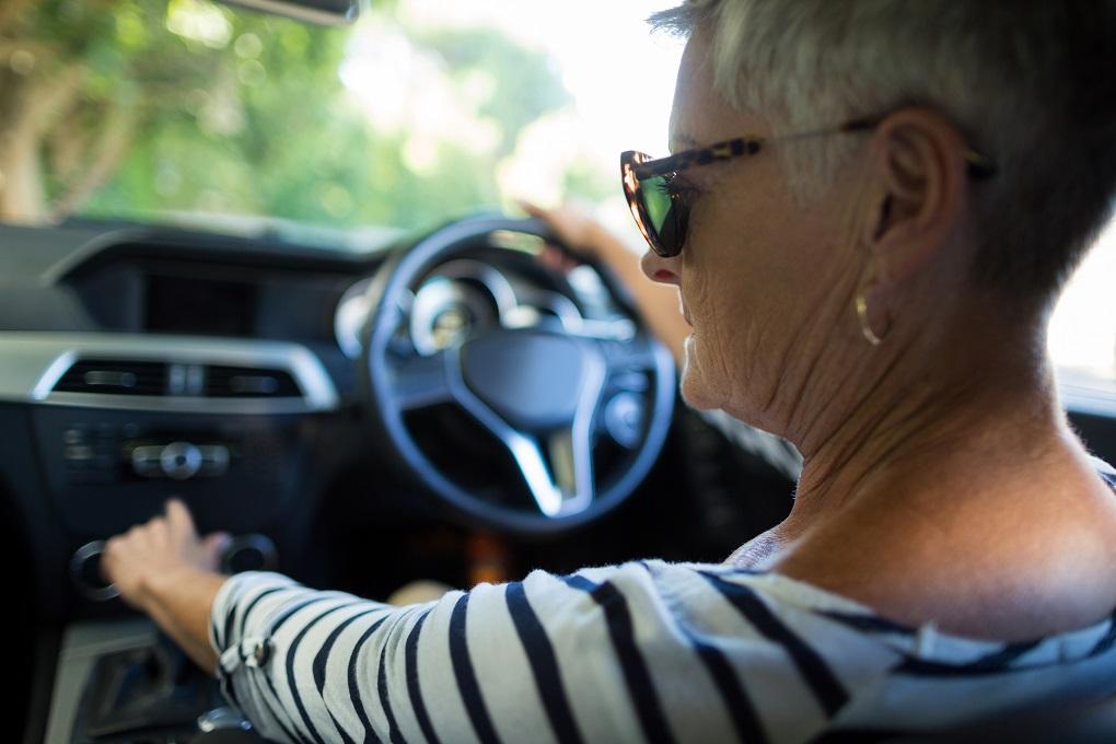 Rear view of serious senior woman driving car