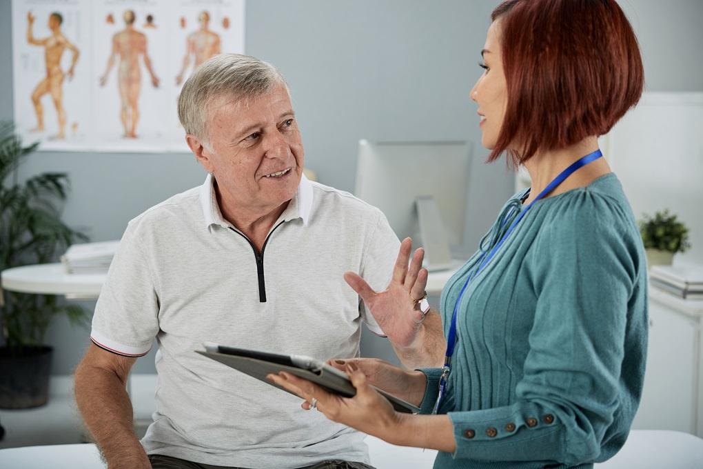 Senior man talking to insurance agent in medical office